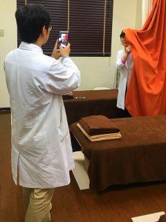 撮影に付き添う、鍼灸師学科の後藤先生。